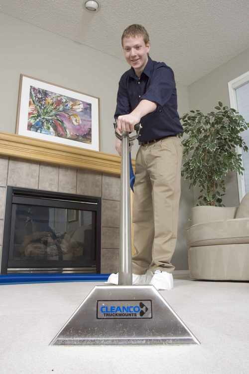 Carpet Cleaning attending to carpet with his cleaning equipment