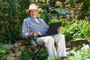 Elderly Man in Garden on Laptop